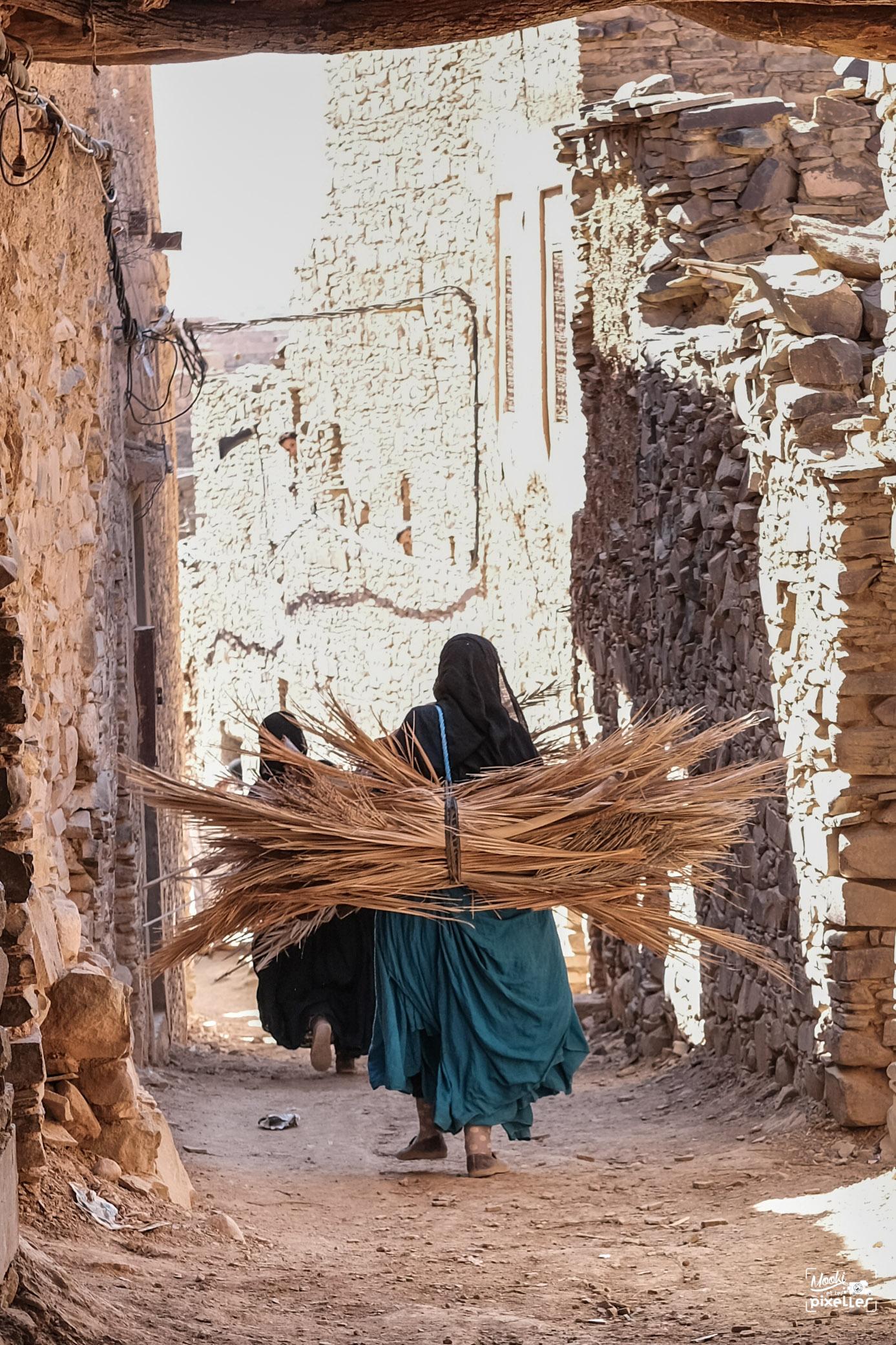 Femme transportant des palmes au Maroc
