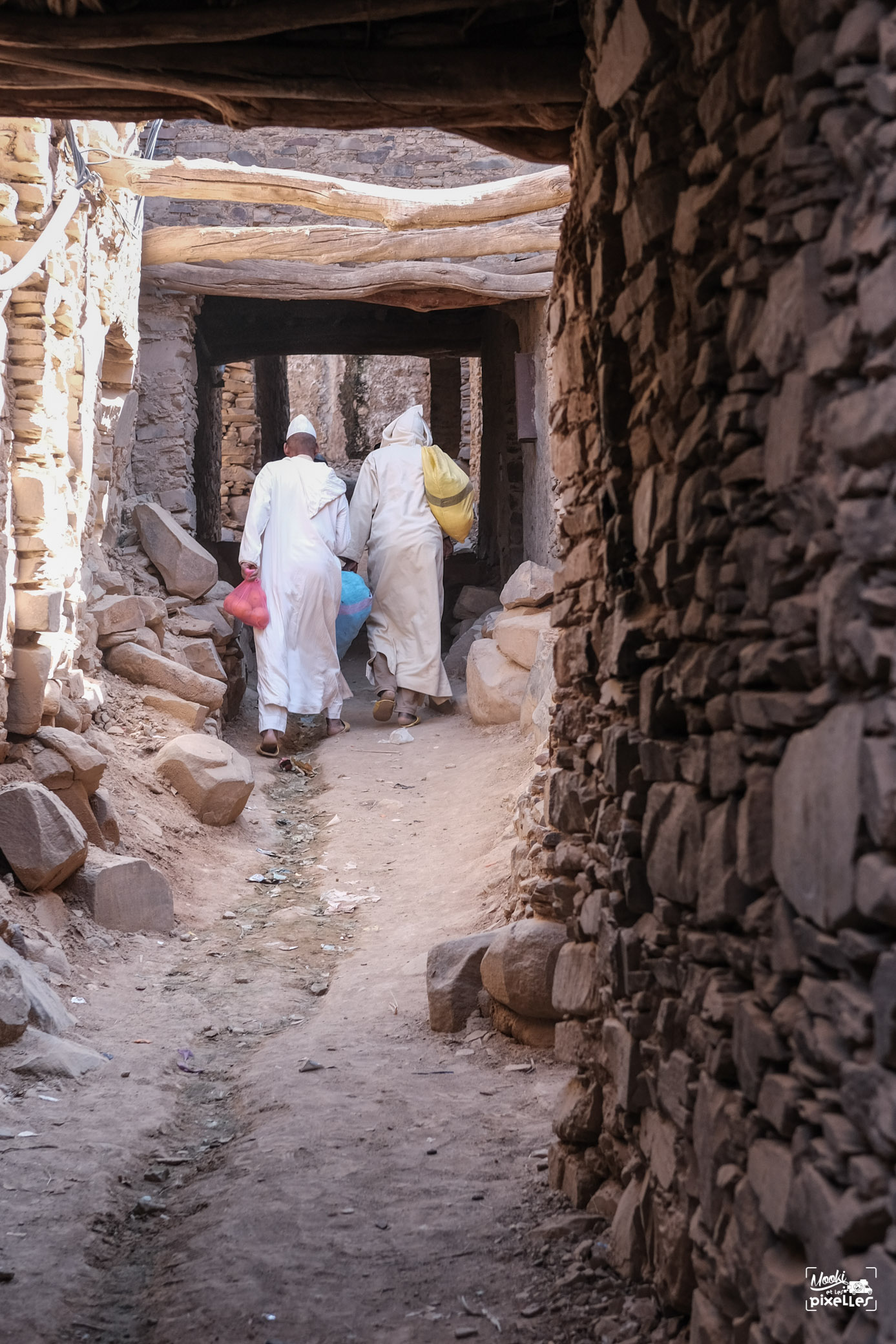 Hommes traversant une ruelle d'un petit village au Maroc