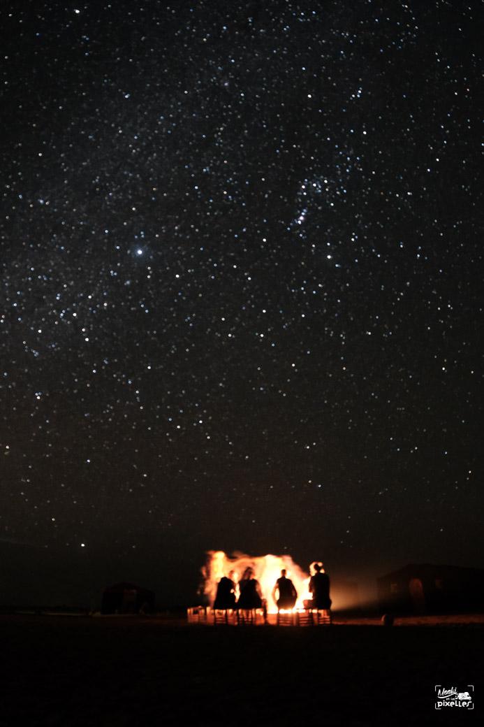 Des copains autour du feu sous la voie lactée