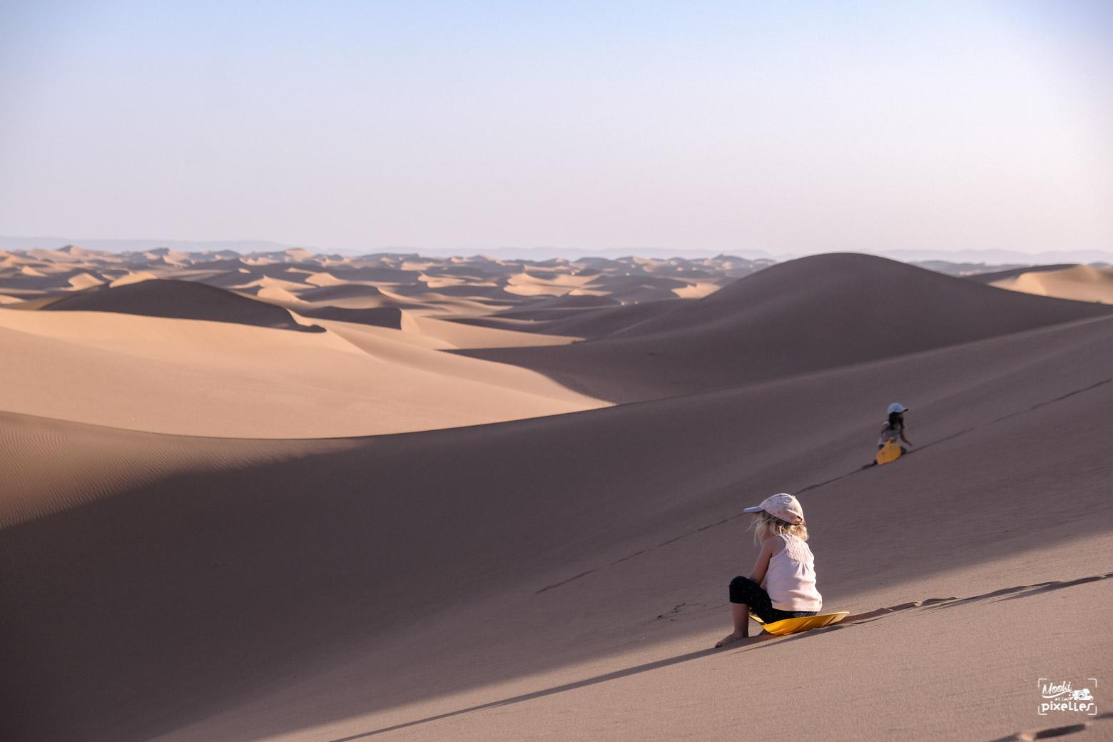 Les filles font de la luge sur les dunes du Sahara