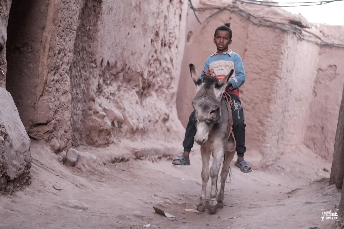 Un enfant se promène à dos d'âne dans un ksar au Maroc