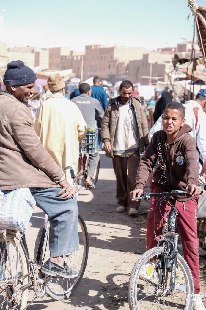 adultes et enfants à vélo dans le souk au maroc