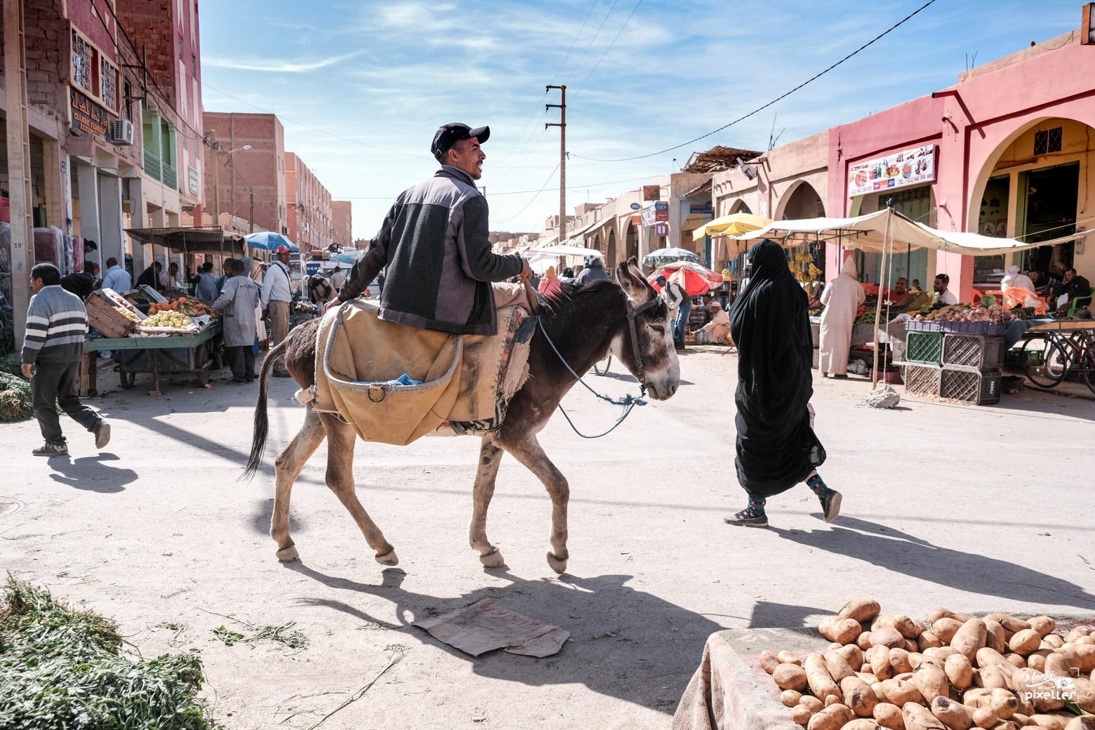 Un homme sur le dos d'un âne dans une rue du souk