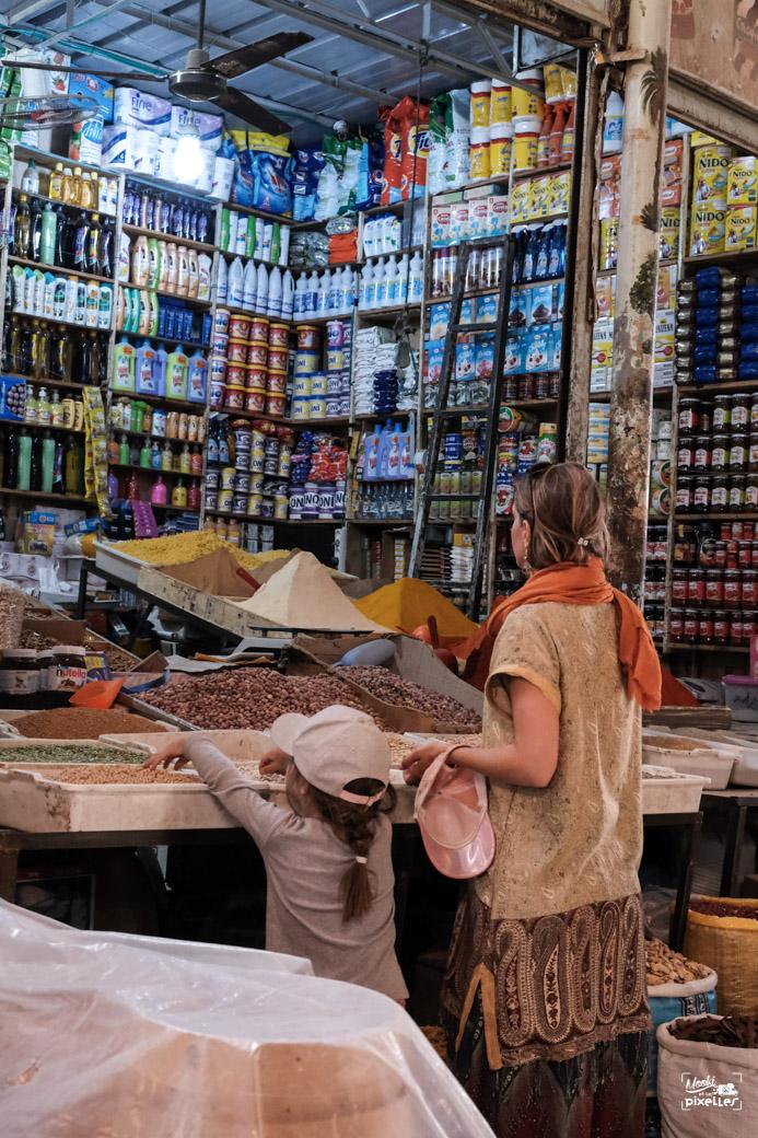 Mère et fille devant une boutique remplie de produits divers